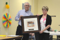Board secretary Marg Nicholson presents Clauge Robinson with a Tom Thomson print to honour his many years of service as board chair of the North Hastings Family Health Team.